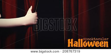 Graphic image of spooktacular Halloween text against cropped hand holding curtain at stage
