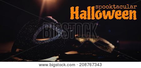 Graphic image of spooktacular Halloween text against masquerade masks on stage