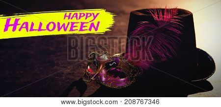 Digital image of happy Halloween text against masquerade masks and hat