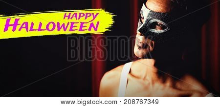Digital image of happy Halloween text against man in masquerade mask