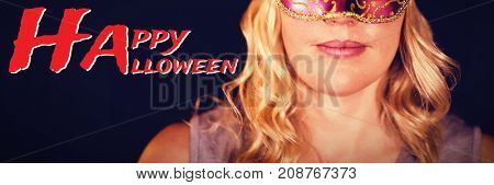 Graphic image of Happy Halloween text against portrait of woman in masquerade mask