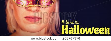 Digital image of time to Halloween text against close-up portrait of woman in masquerade mask