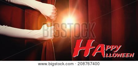 Graphic image of Happy Halloween text against cropped hands holding curtain at stage