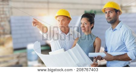 Architects looking away while holding blueprint against workshop