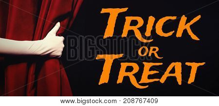 Graphic image of trick or treat text against cropped hand holding stage curtain