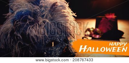Digital image of happy Halloween text against masquerade masks with glove and hat