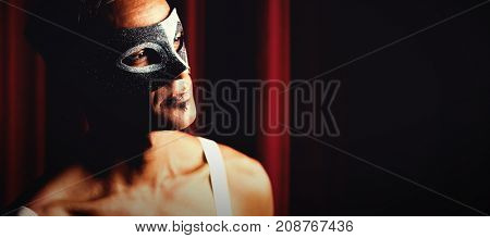 Thoughtful man in masquerade mask at stage