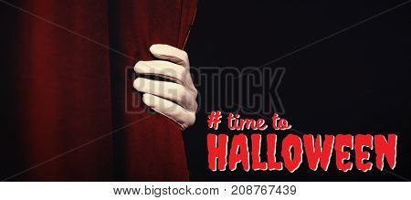 Digital composite image of time to Halloween text against cropped hand in glove holding curtain