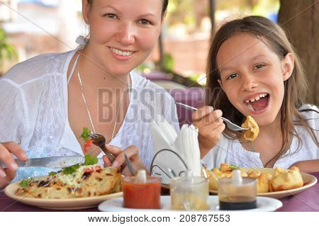 happy mother and daughter eating in cafe together