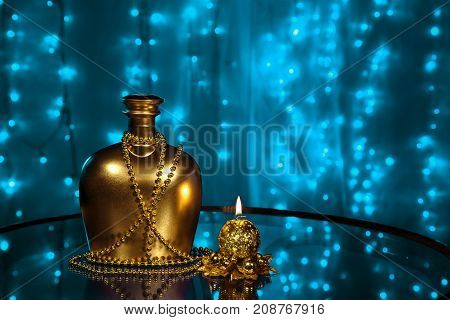 A bottle of brandy and candle in New year and Christmas on blurred blue background