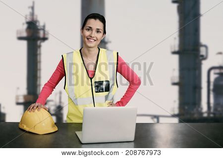 Portrait of female architect wearing reflective clothing against exterior of factory
