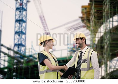Architects in reflective clothing doing handshake while holding tablet computer against work in progress in the city