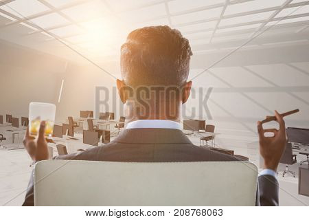Rear view of businessman holding whisky glass and cigar against computers in office