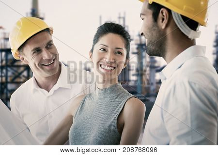 Happy architect discussing over blueprint against image of factory