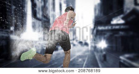 Male athlete running from starting blocks against white dust powder