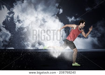 Confident male athlete running from starting blocks against splashing of dust powder