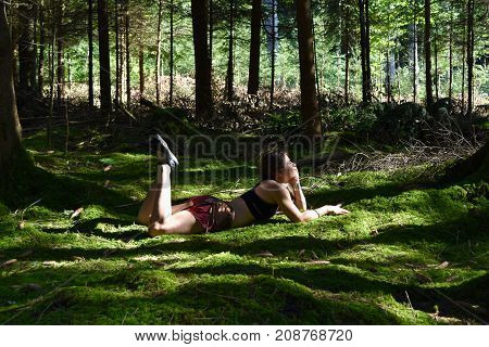 Women is day dreaming in the forest, lying on her belly.
