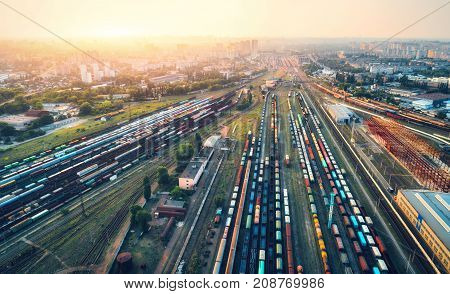 Cargo trains. Aerial view of colorful freight trains. Railway station. Wagons with goods on railroad. Heavy industry. Industrial scene with trains, city buildings and sky at sunset.Top view from drone