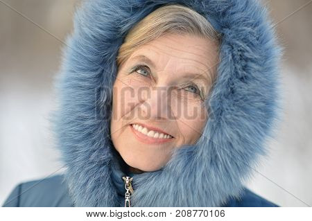mature woman in winter clothes posing outdoors, in good mood