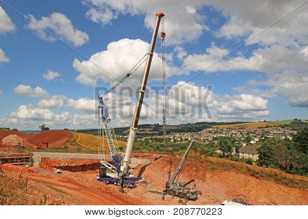 Cranes laying a concrete bridge beam for a new road