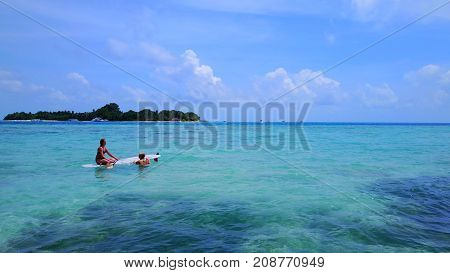 Aerial flying drone view of Maldives white sandy beach 2 people young woman relaxing on paddleboard on sunny tropical paradise island with aqua blue sky sea water ocean 4k.