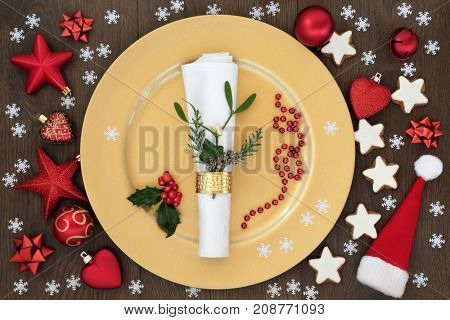 Christmas table place setting with gold dinner plate, napkin with cedar, mistletoe and holly, santa hat, gingerbread biscuits and bauble decorations on oak wood background.