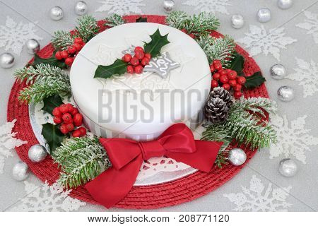Festive iced christmas cake with red bow, holly, fir, snowflake and bauble decorations with silver foil wrapped chocolates on glitter background.