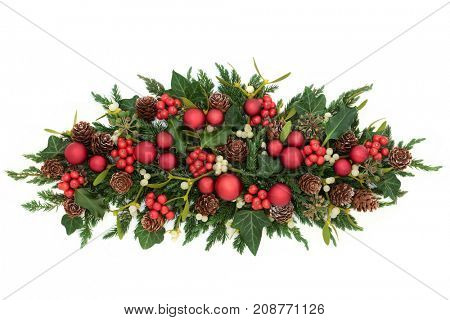 Christmas table decoration with red bauble decorations, holly, ivy, mistletoe, fir and pine cones on white background.