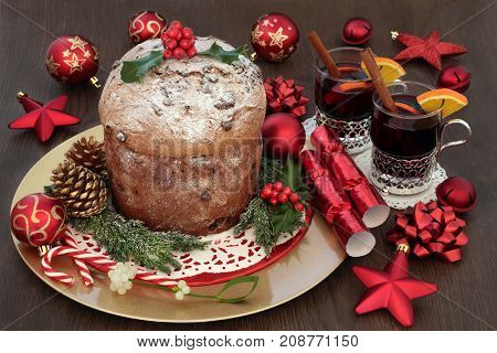 Chocolate panettone christmas cake with mulled wine, bauble decorations, holly, mistletoe, fir, gold pine cones on oak table background.
