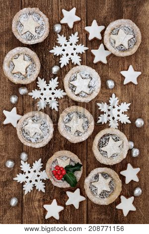 Mince pies and gingerbread biscuits with holly, snowflake bauble decorations and foil wrapped chocolates on oak wood background.