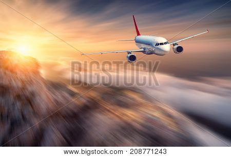 Airplane mith motion blur effect is flying over low clouds at sunset. Landscape with passenger airplane, blurred clouds, mountains, sun. Passenger aircraft. Business travel. Commercial plane. Concept