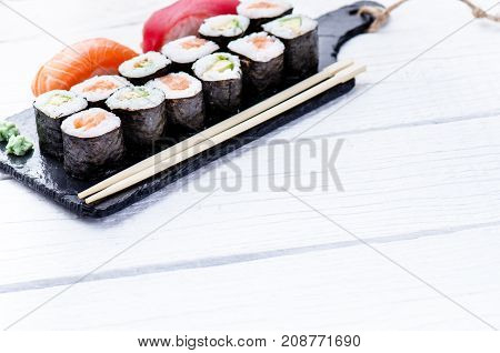 Sushi set served on a black slate. Sushi rolls and sashimi on a wooden white table. Seafood. Raw fish. White background. Wasabi.