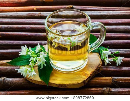 Glass cup of herbal tea jasmine tea and jasmine flowers on an old wooden table with a blurred green natural background. The concept of tea