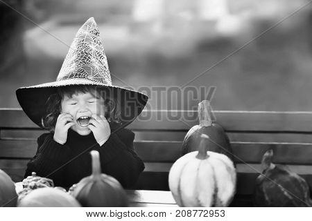 Happy little child with pumpkins having fun. Halloween decorations black and white greeting card.
