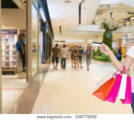 Female walks hands holding shopping bags and credit card in the mall