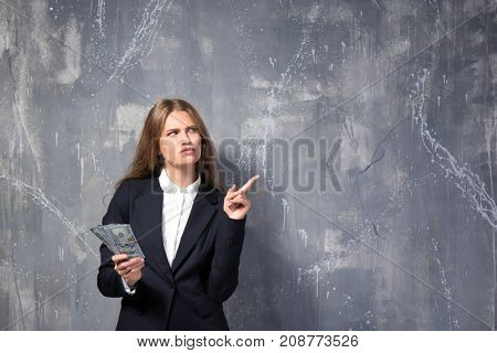 Beautiful young woman with dollar bills on grunge background
