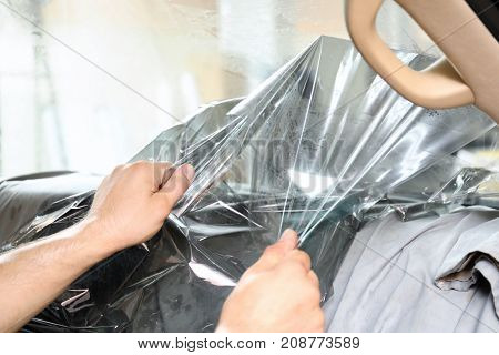 Worker removing film from car window prior to tinting