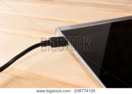 Charging the tablet. How to charge the battery. The charging cable and the tablet.
