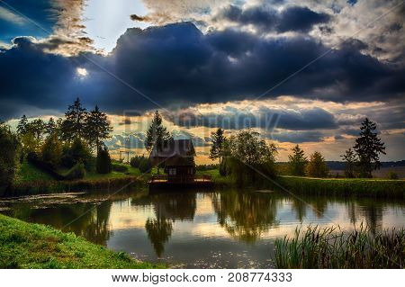 house by the lake on a background of colorful evening sky at sunset beauty of nature Belarus