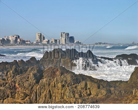 WINTER SEASCAPE, WITH ROUGH SEAS, AND WHITE WAVES WASHING OVER SOME BOULDERS