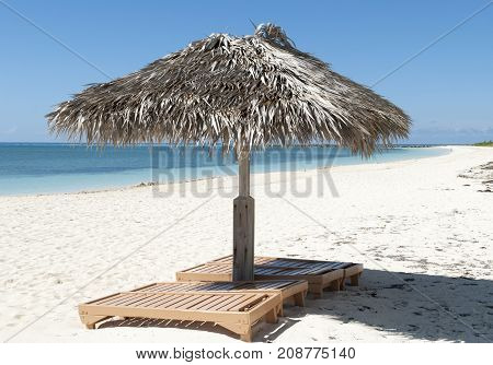 Straw umbrellas with chairs on Grand Bahama island Coral beach (Freeport Bahamas).