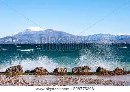 Landscape of a lake with waves and squirts on a windy day background with alpine mountains