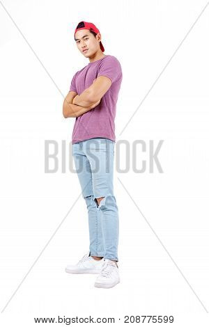 Handsome muscular young Asian man in casual purple T-shirt red cap fashionable blue jean and arm cross isolated on white background