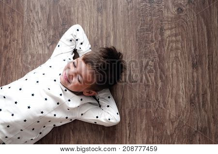 Little Boy Lies On The Warm Floor Of The House