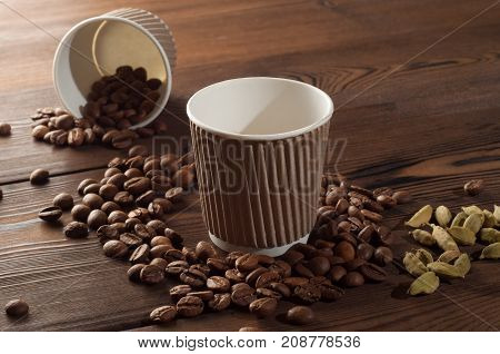 Espresso in paper cup on a wooden background with scattered coffee beans
