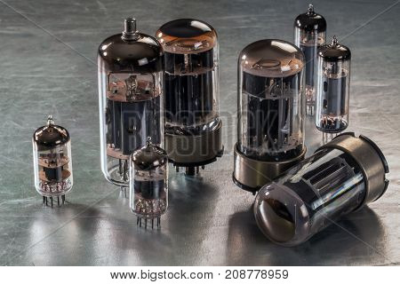 Radio tubes of different sizes lie on a metal surface
