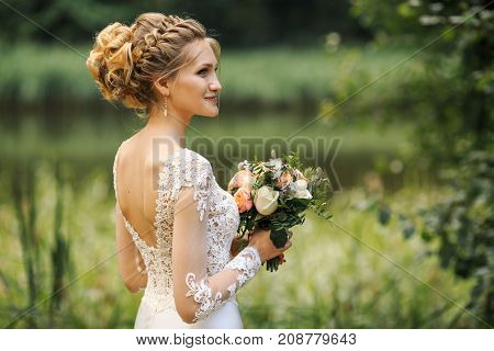 Young Beautiful Bride In White Dress Is Posing On A Wedding Walk In The Forest. Wedding Day.