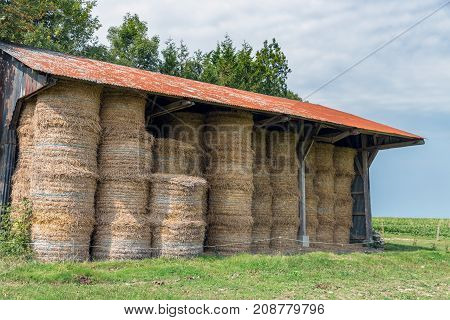 Rural landscape and open barn with pile of haystacks in Normandy, France