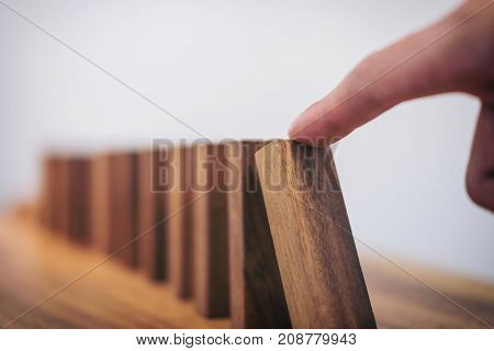 Risk and strategy in business Close up of businessman hand gambling starting push wooden block on a line of domino.