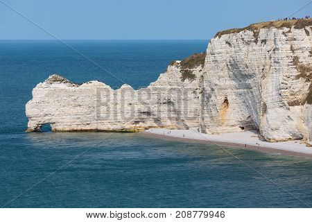 Limestone cliffs with people on top of it near Etretat in Normandie, France